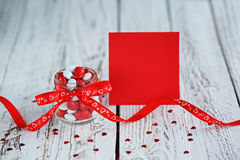 Valentine`s day card with Colorful candy jar decorated with a red bow on light wooden background. Stock Image