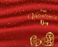 Valentine`s Day card with gold heart shape on red silk background Royalty Free Stock Image