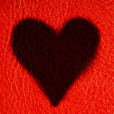 Valentine's day card. Heart love symbol on red leather background Stock Image