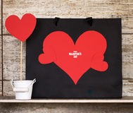 Valentine`s Day card with paper hearts and gift bags. Stock Photos