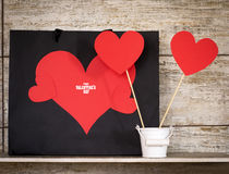 Valentine`s Day card with paper hearts and gift bags. Royalty Free Stock Photo