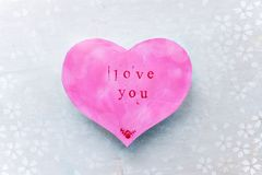 Valentine`s day card in the shape of a pink heart with the word love you royalty free stock photography