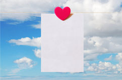 Valentine's Day card with sky background. Pattern for Valentine's Day card with sky background and white sheet of paper held by heart shaped pin Stock Photo