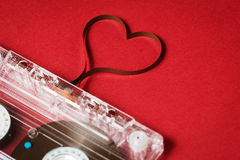 Valentine's day card template. Audio cassette with magnetic tape in shape of heart on red background Stock Photos