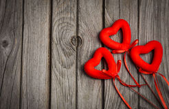 Valentine's day card with three red hearts on rustic wooden background. Stock Photos