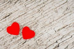Valentine`s day card, two red hearts on white wooden table stock images