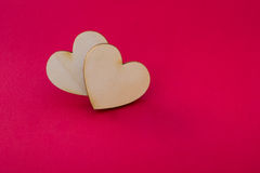 Valentine's day card with two wooden hearts symbol on red surfac Royalty Free Stock Photo