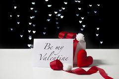 Valentine`s Day card and white gift box with red ribbon and heart shaped fabric on light bokeh background stock photography