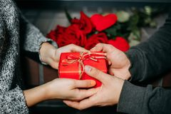 Valentine`s day celebrating. Hands of couple holding red gift bo. X and roses on background. Giving present, surprise, relationships, togetherness, love, dating Royalty Free Stock Photos