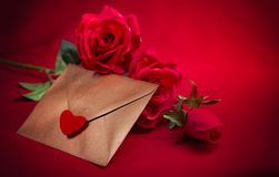 Valentine concept, love letter, rose on the dark background. Valentine`s day celebration with romantic items: sealed love letter, a rose on a dark red background Royalty Free Stock Photography