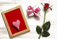 Valentine`s Day. Champagne, roses, hearts, gift basket with bow on a white wooden texture background royalty free stock photo
