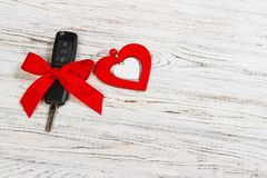 Valentine`s day or christmas car key gift. Car key with a red ribbon and heart on white wooden table.  Royalty Free Stock Image