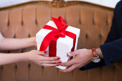 Valentine`s day or christmas concept - gift box in male and fema Stock Images