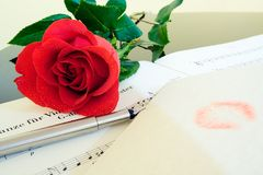 Valentine's Day Composition. A letter with lipstick kiss with a calligraphy pen and beautiful red rose against a piano top and music score. Warm lighting Stock Photos