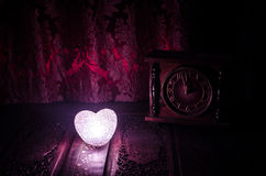 Valentine's Day composition with sweet burning multicolored heart on dark background and old vintage clock, time and love royalty free stock photography