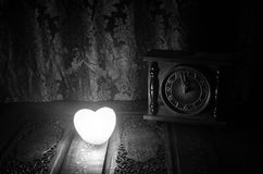 Valentine's Day composition with sweet burning multicolored heart on dark background and old vintage clock, time and love concept, Royalty Free Stock Photos