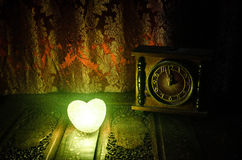 Valentine's Day composition with sweet burning multicolored heart on dark background and old vintage clock, time and love concept, Stock Image
