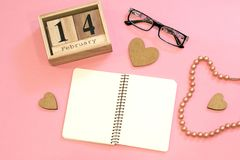 Valentine`s Day composition with wooden calendar, hearts, glasses, chaplet and spiral notebook on pink background. 14 february stock photo