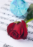 Valentine's Day Concept. Red rose and gift box on notesheet Stock Image