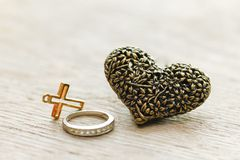Black silver heart on wooden background with old Christian Cross. Valentine`s day concept - Black heart jewellery pendant on wooden background royalty free stock photography