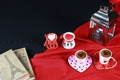 Valentine`s day concept. Coffee in heart shaped cup with candle and notebook on black background. Red background stock images