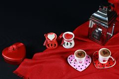Valentine`s day concept. Coffee in heart shaped cup with candle and red gift box on black background. Red background royalty free stock photos