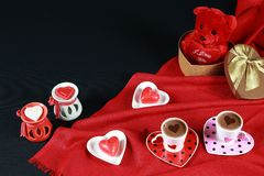Valentine`s day concept. Coffee in heart shaped cup with candle and teddy bear in gift box on black background. Red background royalty free stock photo