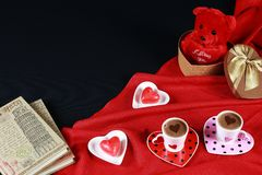 Valentine`s day concept. Coffee in heart shaped cup with candle and teddy bear in gift box with notebook on black background. Valentine`s day concept. Coffee in stock image