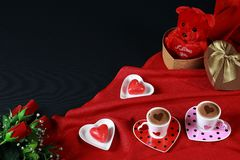Valentine`s day concept. Coffee in heart shaped cup with candle and teddy bear in gift box with red roses on black background. Valentine`s day concept. Coffee royalty free stock photos