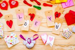 Valentine`s day holiday. cute decorations: paper hearts, clips, origami envelopes on wooden background. Valentine`s day concept. decorations for the holiday Royalty Free Stock Photos