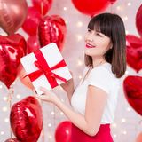 Valentine`s day concept - dreaming woman holding gift box over red balloons background. Valentine`s day concept - dreaming woman holding gift box over red heart royalty free stock image