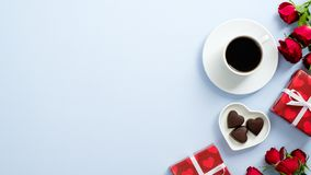 Valentine`s day concept. Gift boxes wrapped red paper, roses flowers, coffee cup and chocolate candies heart shaped on blue