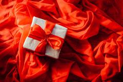 Valentine`s Day concept. Gift with red bow  on the wooden backgr. Ound, Valentines. Valentines gift boxes tied with a red satin ribbon bow on  background. gift Royalty Free Stock Photography