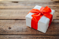 Valentine`s Day concept. Gift with red bow  on the wooden backgr. Ound, Valentines. Valentines gift boxes tied with a red satin ribbon bow on  background. gift Royalty Free Stock Image