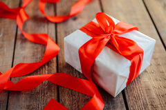 Valentine`s Day concept. Gift with red bow  on the wooden backgr. Ound, Valentines. Valentines gift boxes tied with a red satin ribbon bow on  background. gift Stock Photo