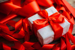 Valentine`s Day concept. Gift with red bow  on the wooden backgr. Ound, Valentines. Valentines gift boxes tied with a red satin ribbon bow on  background. gift Stock Photos