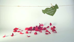 Valentine`s day concept. Green paper heart with wings and congratulation fixed with clothespin on a cord and red hearts. Falling stock video footage