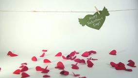 Valentine`s day concept. Green paper heart with wings and congratulation fixed with clothespin on a cord and red hearts. Lifting up stock footage