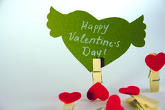 Valentine`s day concept. Green paper heart with wings and congratulation fixed on a clothespin and 4 heart shape. Clothespins on white background Royalty Free Stock Photography
