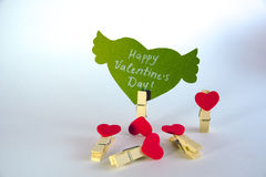 Valentine`s day concept. Green paper heart with wings and congratulation fixed on a clothespin and 4 heart shape. Clothespins on white background Stock Images