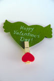Valentine`s day concept. Green paper heart with wings and congratulation fixed on a clothespin on white background. Valentine`s day concept. Green paper heart Royalty Free Stock Image