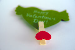 Valentine`s day concept. Green paper heart with wings and congratulation fixed on a clothespin on white background. Valentine`s day concept. Green paper heart Royalty Free Stock Photo
