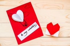 Valentine`s day holiday. hand made gift card with a heart balloon and an origami heart on rustic background. Valentine`s day concept. hand made craft. gift card Royalty Free Stock Images