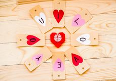 Valentine`s day holiday. hand made paper hearts labels on rustic background in circle with red origami heart inside Royalty Free Stock Image