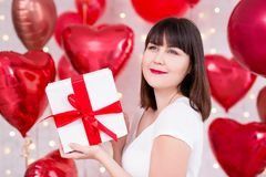 Valentine`s day concept - happy dreaming woman with gift box over red balloons background. Valentine`s day concept - happy dreaming woman with gift box over red stock images