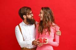 Valentine`s day concept. happy young couple with heart, flowers, gift on red stock image