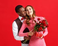Valentine`s day concept. happy young couple with heart, flowers, gift on red. Background stock photography