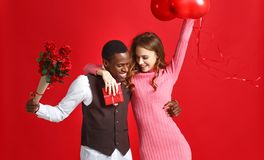 Valentine`s day concept. happy young couple with heart, flowers, gift on red stock photo