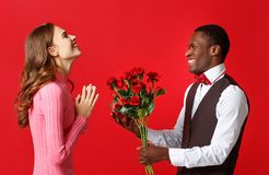Valentine`s day concept. happy young couple with heart, flowers, gift on red royalty free stock photos