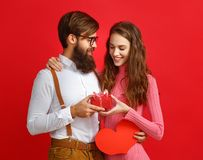 Valentine`s day concept. happy young couple with heart, flowers, gift on red stock images